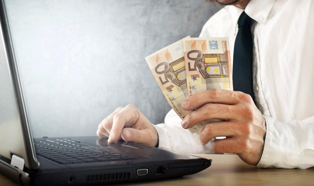 мужчина за ноутбуком с деньгами